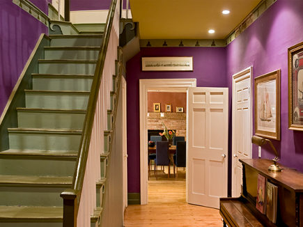 purple foyer with green ceiling trim and green-painted staircase