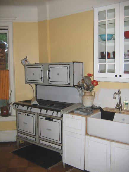 unfitted kitchen before renovation with antique stove and 1940s cabinets