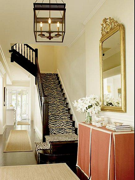 vintage gold leaf over mantel mirror in foyer with zebra carpet stair runner