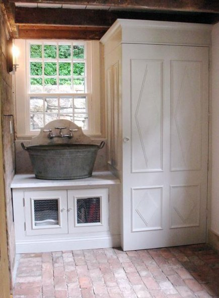 washtub basin sink with a marble counter and stacked washer dryer in a custom laundry room