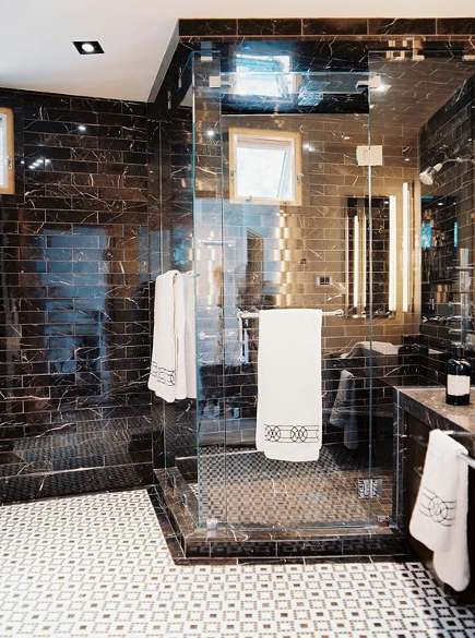 bathroom with black and white marble subway tiles and white mosaic tile floor with black accents