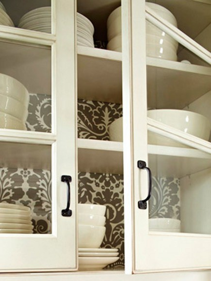 taupe and white damask pattern wallpaper in the back of a glass-front upper kitchen cabinet