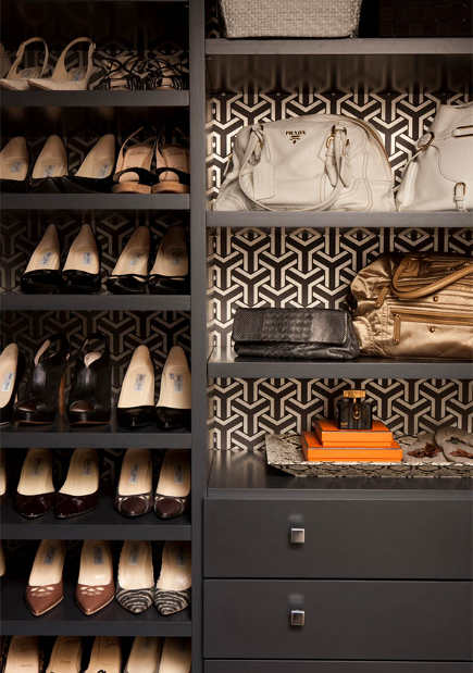 brown and white stylized wishbone pattern wallpaper behind closet shelves