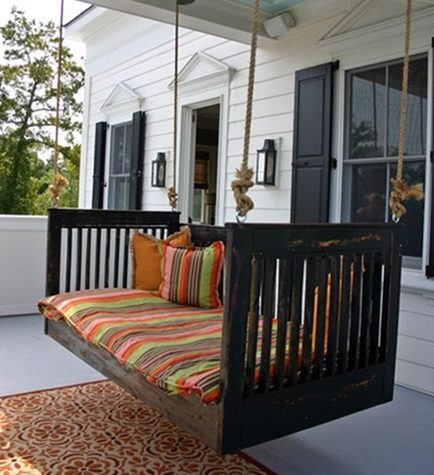 swinging porch beds - custom dark stained swinging porch bed with orange and green striped mattress and pillows - via Atticmag