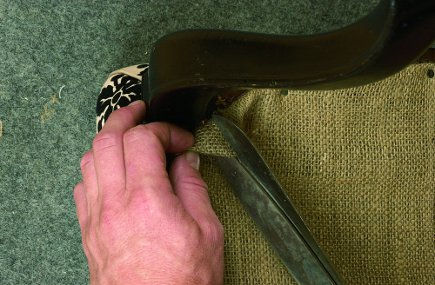 attaching the dust cover to the bottom of an upholstered chair from The Upholsterer's Handbook