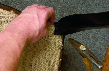 fitting the dust cover on the bottom of a newly upholstered chair around the leg, from The Upholsterer's Handbook