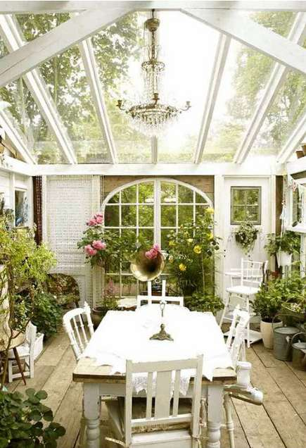 greenhouse rooms - cottage style conservatory with repurposed doors, windows, and raw wood flooring - busydoor via atticmag