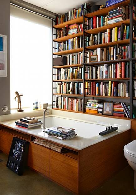 bookcases in a wall behind bathtub in bathroom - the library soup via atticmag