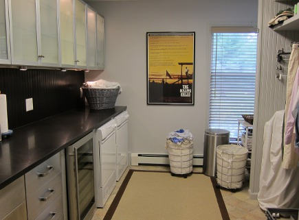 view of finished, repainted laundry room with black beadboard backsplash