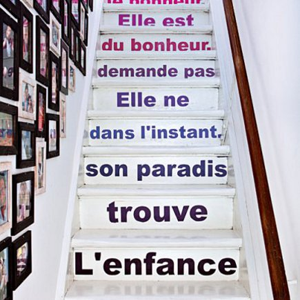 white-painted staircase with French words on the risers