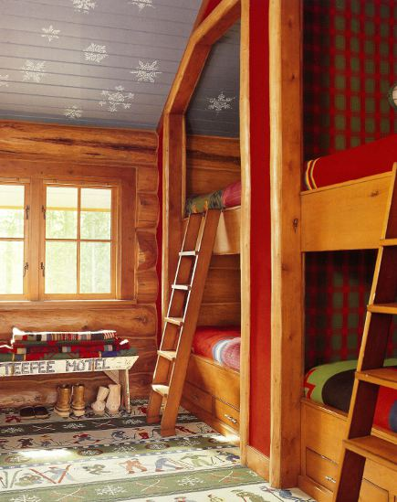 bunk beds in the kids room of an Idaho timber vacation home with red, green and blue winter theme decor