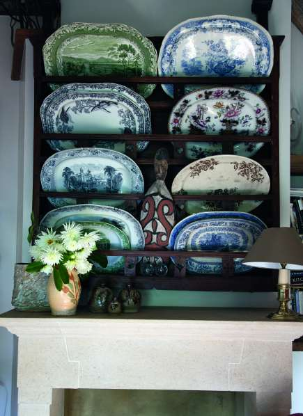 plate rack with transferware platters installed above a fireplace from A Living Space by Kit Kemp
