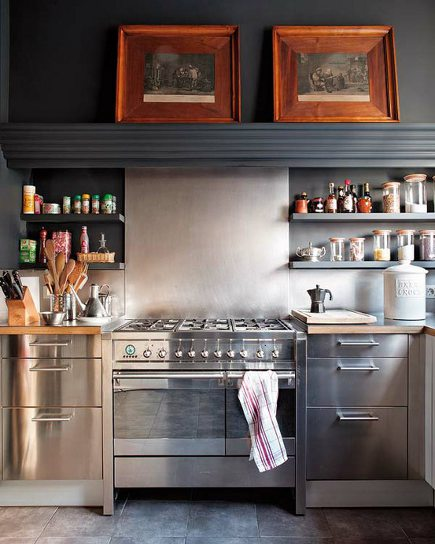 stainless steel range and base cabinets with dark gray hood above them