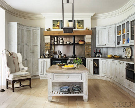 Kit Kemp's oval kitchen with white limed-oak cabinets and a bottle green Aga cooker