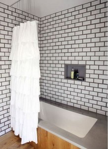 bold tile grout - white subway tile bathroom with dark grout and and a pine floor - design sponge via atticmag