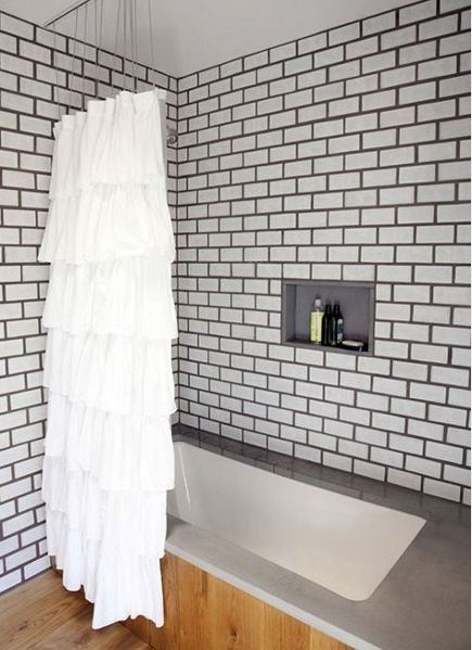 white subway tile bathroom with dark grout and and a pine floor
