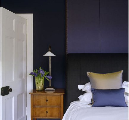 bedroom by John Minshaw with blue-violet walls and a black upholstered headboard