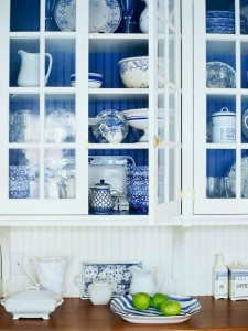 white kitchen cabinet with glass doors and cobalt blue beadboard behind the shelves
