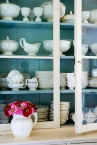 white china cabinet with turquoise-painted back and shelves