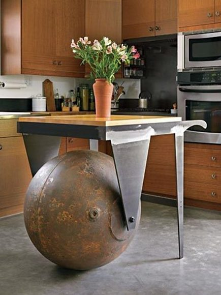 A salvaged marine steel buoy ball is repurposed into a functional kitchen work table.