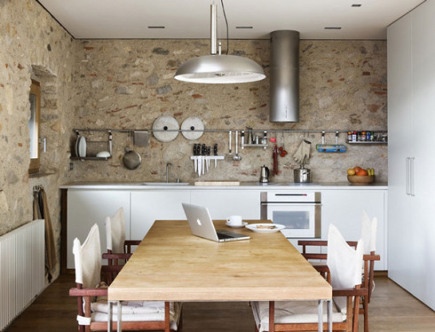 contemporary Spanish kitchen with stone wall