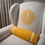 white upholstered wing chair with contrasting saffron color monogram