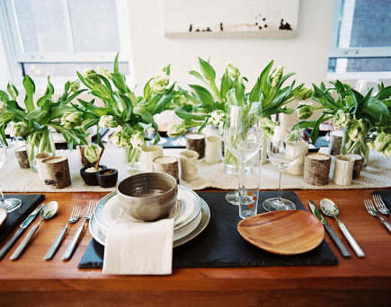 informal table set with organic-feel wooden plates, pottery bowls and birch-wrapped candles