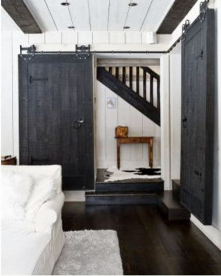 double interior barn doors - black painted sliding barn doors used in a pair on a corner - chiccoles via Atticmag