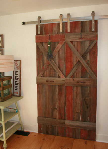 double interior barn doors - pair of red painted salvage sliding barn doors in a kitchen - the polished pebble via atticmag