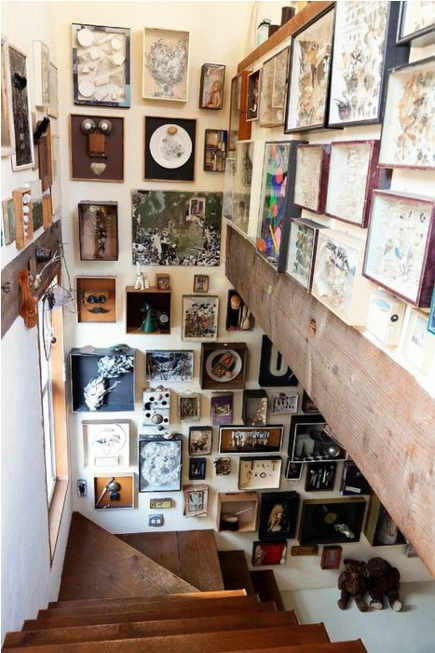 narrow stairwell hung with pictures and objects on three walls