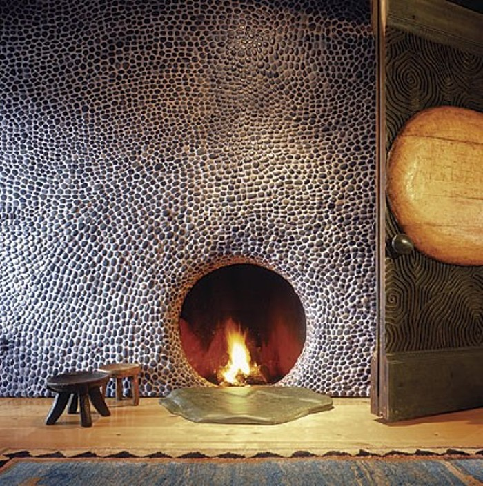 river rock covered fireplace wall with circular firebox opening - fine home building via atticmag
