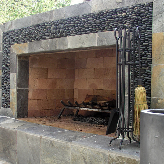 river rock and slate outdoor fireplace surround - Studio H Landscape Architecture via Atticmag