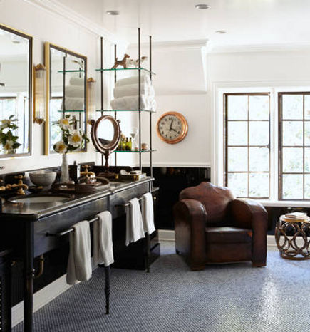 Large bath with vintage upholstered seating and an antique vanity and clock
