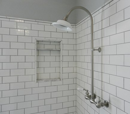 white subway tile shower with exposed shower set