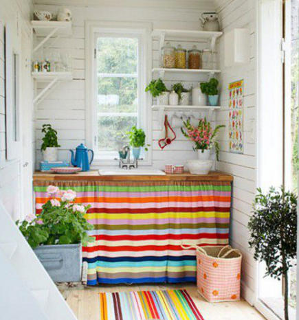colorful striped sink skirt and rug in a white cottage kitchen