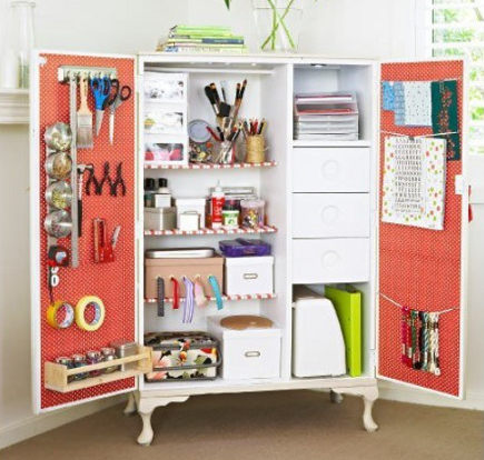crafts room ideas - craft room armoire that contains equipment on shelves and hanging from the doors - the embellished nest via atticmag