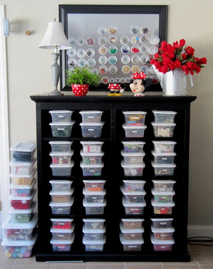 crafts room ideas - cabinet housing matching plastic storage bins with storage cups on a magnetic board - sew many ways via atticmag