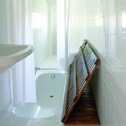bathtub hidden under wooden slatted floor