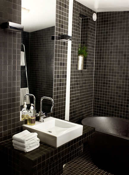 modern black bathroom with mosaic field tiles on walls and floor - Jimmy Schonning via Atticmag