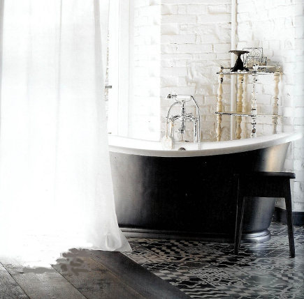 Black bathroom by Paola Naovne with patterned Morrocan tile and black slipper tub