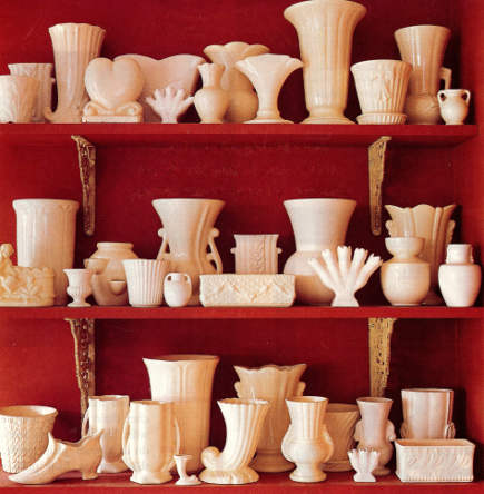 white pottery displayed against a dark red wall and shelves