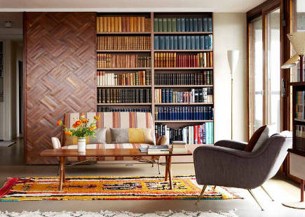 sitting room with parquet sliding barn-style door and mid-century furniture