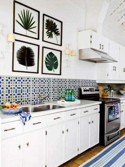 white kitchen with blue and green geometric tile backsplash and blue and white striped rug