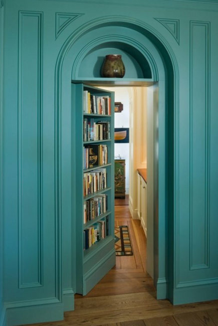 door concealed behind a bookcase in a paneled wall