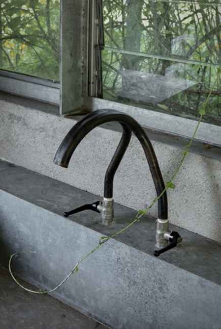 galvanized steel faucet on a concrete sink in an Italian garage refitted as a garden shed and entertaining space