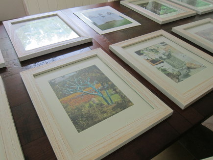 arranging framed pictures to hang on a wall