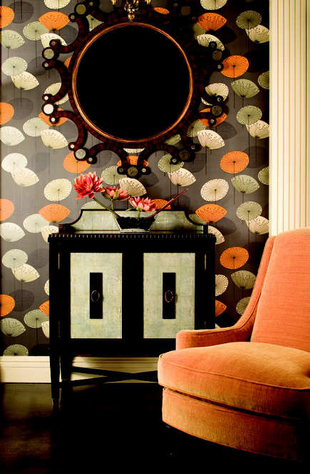 orange home decor - room with orange and black print wallpaper accented by orange upholstered chair - pinterest via atticmag