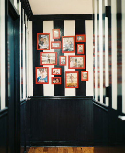 Black and white vertical stripes on a picture wall in a hallway with black paneling – Lonnymag via Atticmag
