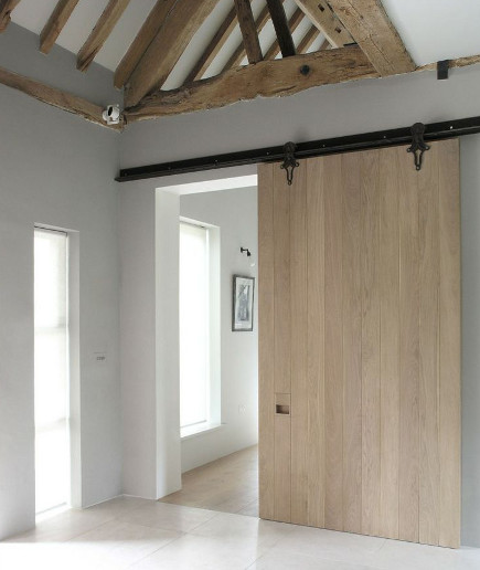 New natural wood sliding interior barn door in a restored English barn – Mclaren.Excell via Atticmag