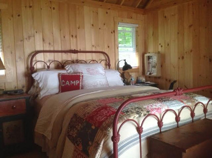 pine-paneled master bedroom of the Maine Lake Camp house - Atticmag
